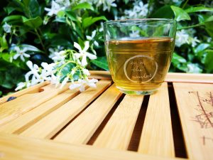 Glass of green tea on a wood table outside